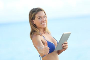 Beautiful woman in bikini using tablet and showing thumb up