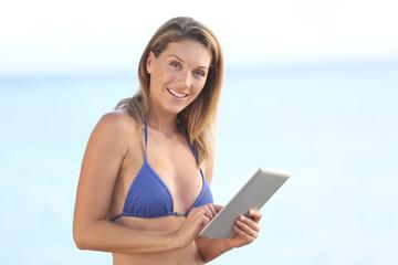 Beautiful blond woman in blue bikini using tablet