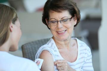 Senior woman receiving flu vaccine