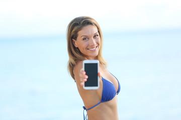 Woman in bikini holding smartphone towards camera