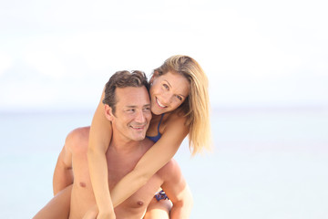 Cheerful 40-year-old man giving piggyback ride to woman