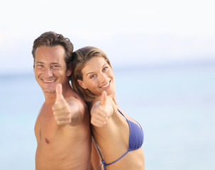 Middle-aged couple in swimsuit showing thumbs up