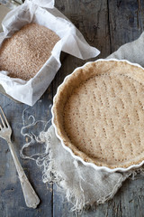 raw wholemeal dough for tart on ceramic mold for quiche