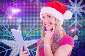 Composite image of festive blonde using tablet pc