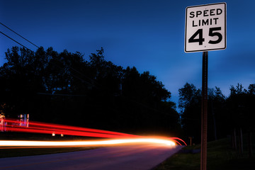 Long exposure of cars passing by a speed limit sign.
