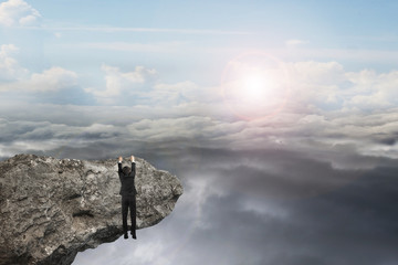businessman hand hanging on cliff with natural sky daylight clou