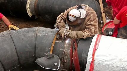 Welder is welding the pipeline in trench