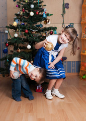Joyful kids playing in a Christmas tree (3 years and 6 years)
