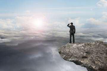 businessman looking on cliff with natural sky daylight cloudscap