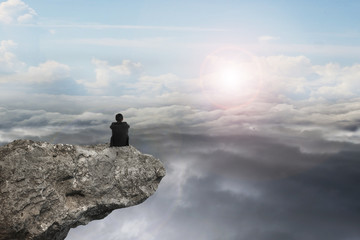 businessman sitting on cliff with natural sky daylight cloudscap