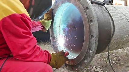 Welder welding a pipe on a terrain