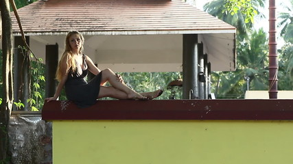 girl sitting on the fence posing near the banyan and looking
