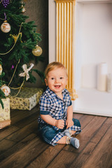 Smiling baby-boy sitting under Chritmas tree near fireplace