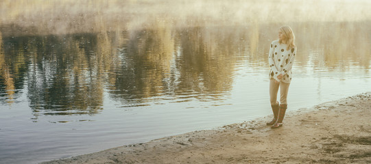 lonely beautiful girl walks on river bank early in morning