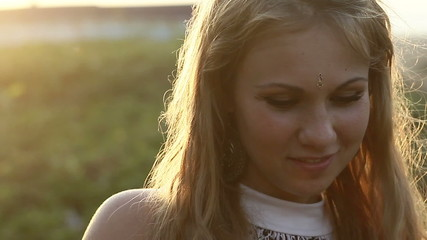 young beautiful blonde girl show her earring at sunset