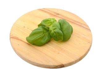 Sprig of fresh basil leaves on a chopping board