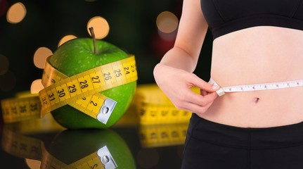 Composite image of fit woman measuring her waist