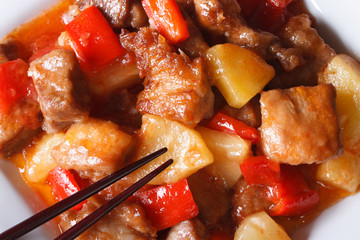 Pork meat with vegetables in sauce macro. horizontal top view