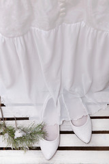 Vintage wedding dress and shoes on a wooden background