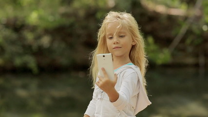 Little girl makes the photo on the phone in the forest near the