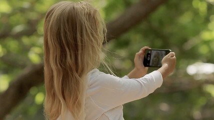 Beautiful little girl with long blond hair photographing herself