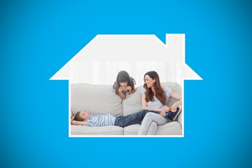 Composite image of mother sitting with her children on sofa