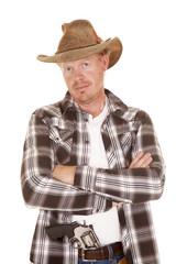 cowboy looking gun in pants arms folded