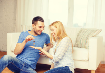 man giving keys to girlfriend or wife at home