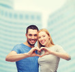 smiling couple showing heart with hands