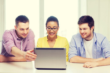 three smiling colleagues with laptop in office