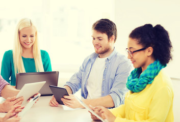 smiling team with table pc and laptop in office
