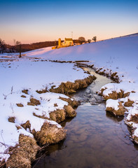 Stream and barn in a snow-covered farm field in eastern York Cou
