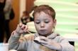 Preschooler paints a cardboard toy