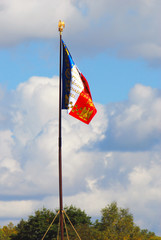 Old French state flag tricolor. Blue sky background.