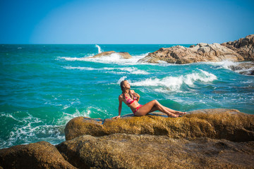 Young sexy woman in red bikini posing In front of sea on the