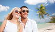 couple in shades over tropical beach background