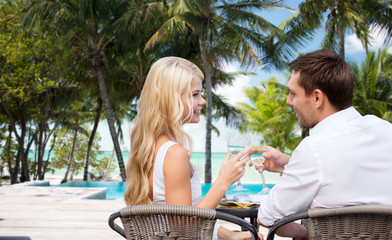 couple drinking wine in cafe on hotel beach