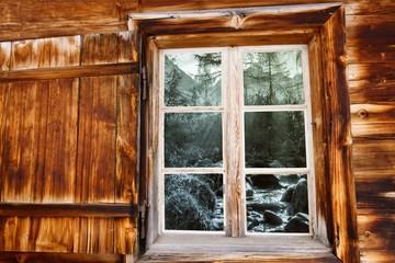 Blick durch das Holzfenster auf den Wildbach in schwarz weiß