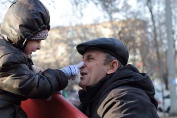 Дедушка с внуком играют на площадке зимой