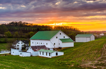 Sunset over a barn and farm fields in rural York County, Pennsyl