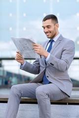 young smiling businessman newspaper outdoors