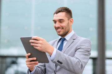 smiling businessman with tablet pc outdoors