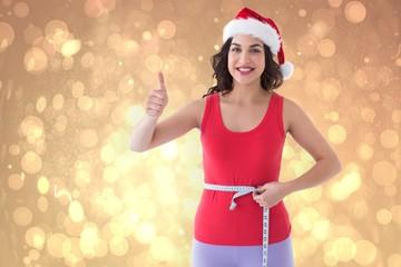 Composite image of festive fit brunette measuring her waist