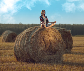 Young woman meditating on haystack
