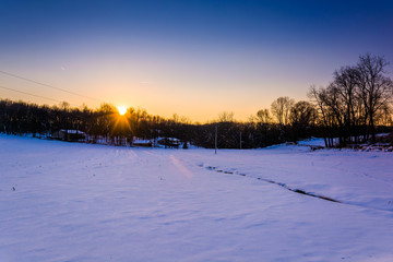 Sunset over a snow-covered farm field in rural York County, Penn