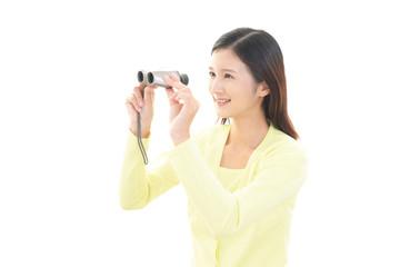 双眼鏡を持つ笑顔の女性