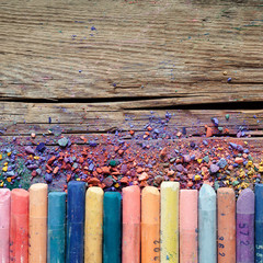 Artistic pastel crayons and pigment dust on rustic wooden backgr