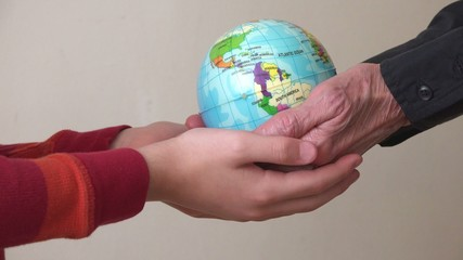 Hands of two generations holding a globe,environmental concept