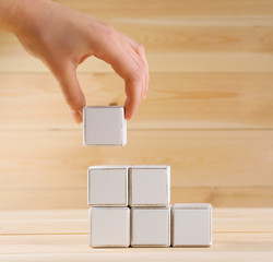 Educational cube in hand, on wooden background