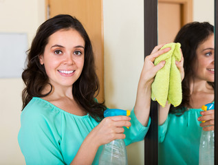 Brunette woman cleaning mirror